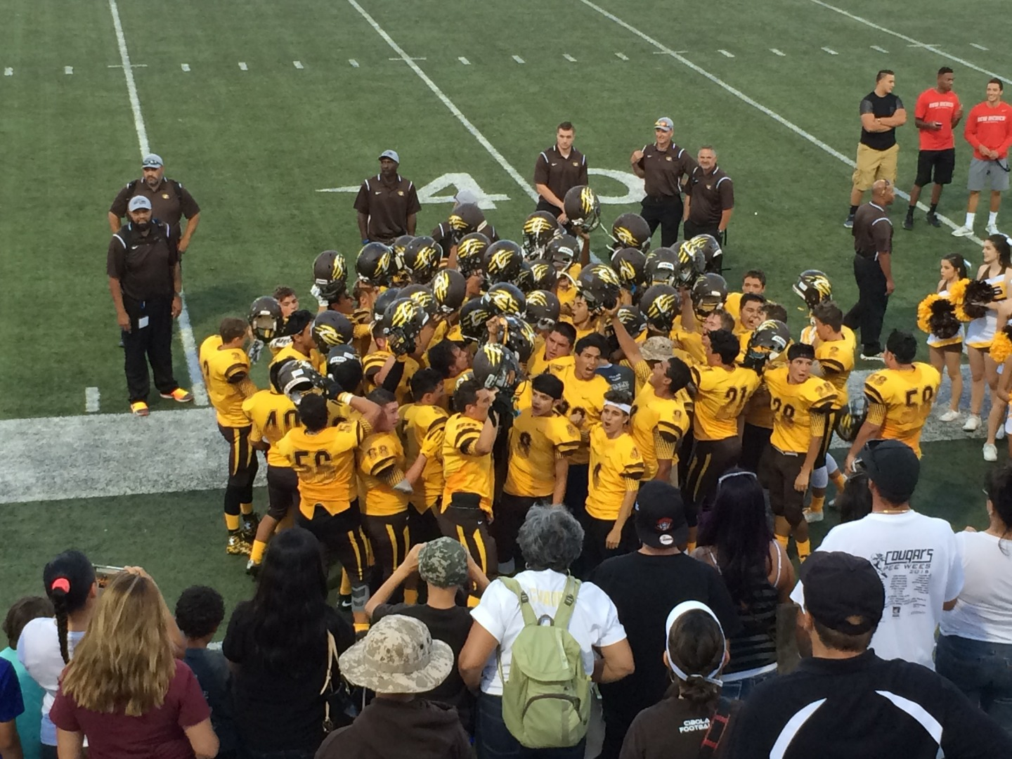 Photo of the football team in a huddle on the side of the field